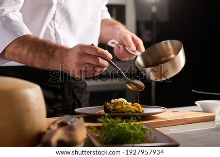 Professional cook in uniform add some spices to dish, decorating delicious meal for guests in hotel restaurant. food, cooking concept