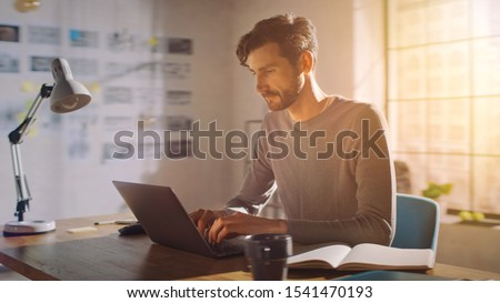 Professional Creative Man Sitting at His Desk in Home Office Studio Working on a Laptop, Concentrated Man Using Notebook Computer.