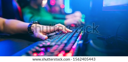 Professional cyber video gamer studio room with personal computer armchair, keyboard for stream in neon color blur background. Soft focus.