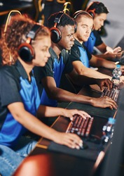 Professional cybersport team wearing headphones participating in eSport tournament, playing online video games while sitting in gaming club or internet cafe