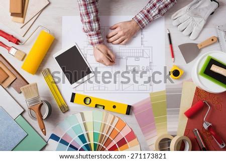 Professional decorator drawing on a house project with work tools, painting rollers and color swatches all around, top view