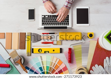 Professional decorator\'s hands working at his desk and typing on a laptop, color swatches, paint rollers and tools on work table, top view