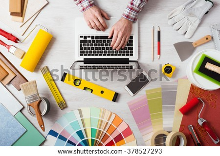 professional decorator 39 s hands working at his desk and typing on a