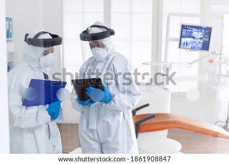 Professional dentists using tablet pc dressed in ppe suit as safety precaution for covid19. Stomatology team in dental office wearing protective suit agasint contagious coronavirus during global
