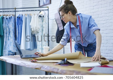 Professional designer in eyeglasses watching video on modern netbook computer while working on sketch of clothing standing at desktop with equipment for tailoring on background with fashion collection