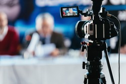Professional digital camera recording presentation of a blurred speaker wearing suit, live streaming concept