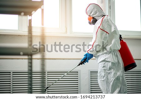 professional disinfector in protective suit holding chemical sprayer and other equipment for sterilization and decontamination of viruses, infectious diseases. coronavirus, COVID-19 epidemic concept Сток-фото ©