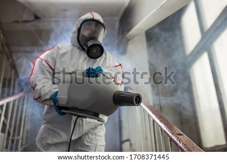 professional disinfector wearing protective biological suit and gas-mask conducts disinfection against coronavirus global pandemic warning and danger. COVID-19, coronavirus concept