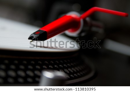 Professional DJ audio equipment - shperical turntable needle on white vinyl record
