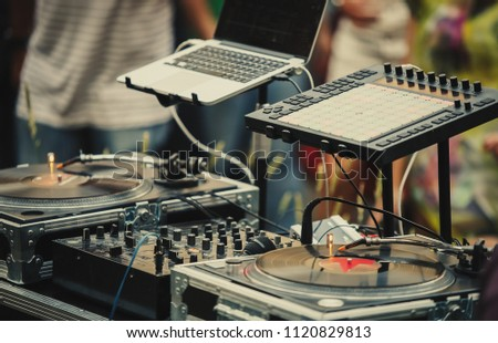 Professional dj audio setup on stage at summer open air music festival.Disc jockey equipment for playing musical tracks on party outdoor.Vinyl records player,midi controller,sound mixer and laptop #1120829813