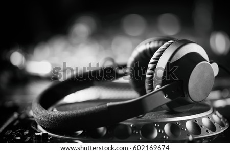 Professional dj headphones on cd disc turntable player.Professional disc jockey audio equipment.Party dj headset technology closeup.Monochrome audio equipment shot.Hifi headset for club disc jockey