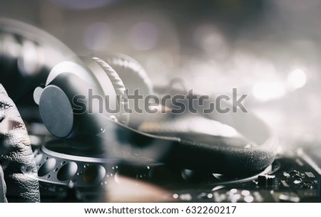 Professional dj headphones on cd player turntable deck in night club.Double exposure effect.Disc jockey audio equipment for parties.Play music,mix tracks on digital turntables hardware