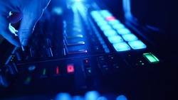 Professional DJ Plays a Beat Sampler with Color Drum Pads and Samples in Studio Environment. Beatmaker Plays edm Tracks on Party in a Nightclub. Electronic Musical Instrument.