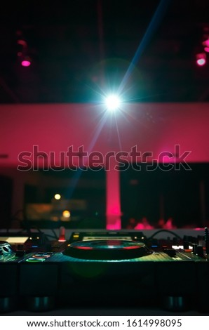 Professional dj setup on table in night club.Disc jockey audio equipment on stage in the music hall.Electronic musical festival background.Bright ray of light  shine in nightclub