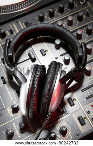 Professional DJ stereo headset on mixing controller