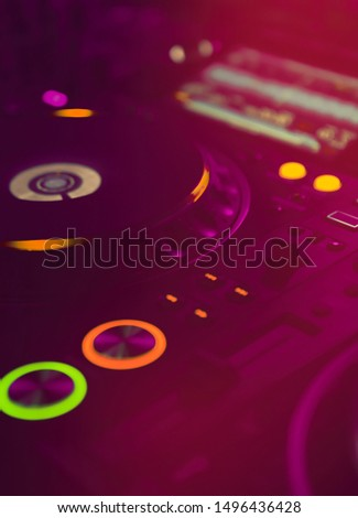 Professional dj turn table in bright red stage lights.Modern cd player turntables for disc jockey.Play edm music on party in night club with top djs audio equipment