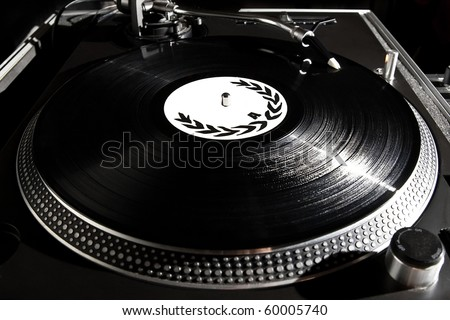 Professional Dj turntable record player playing vinyl disc with music. Analog audio equipment for disc jockey, party, concert. Hip hop DJ scratching records. Turntable needle in focus