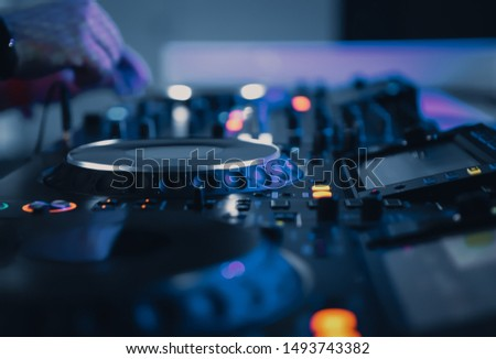Professional dj turntables and sound mixer in blue lights at techno music party.Play musical tracks at entertainment event with disc jockey audio equipment.Digital cd turntables setup in close up