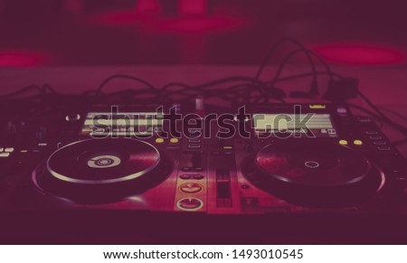 Professional dj turntables on scene in red lights.Hip hop disc jockey cd player setup for nightclub party performance.Play and remix musical tracks with turn table system.Edm music festival stage gear