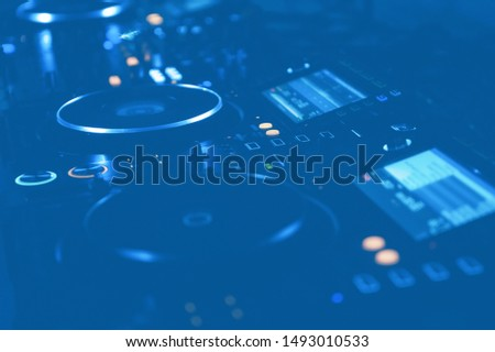 Professional dj turntables setup on stage in blue lights.Hip hop disc jockey turn table system on party in night club.Techno music festival in dark place.Modern audio equipment for djs