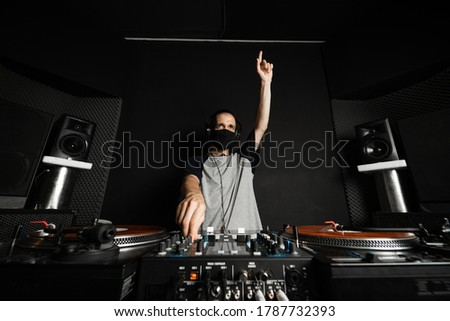 Professional DJ with reusable cloth face mask playing music raising his hand to cheer up the clients of the disco, with orange records and a gray T-shirt with dark blue sleeves Сток-фото ©