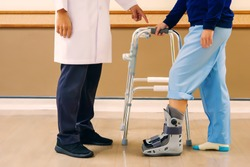 Professional doctor is explaining how to walk by wearing an orthopedic boot and having a walker to help support. medical and orthopedic concept.