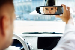 Professional driving. Confident smart man looking into the rearview mirror while driving his car