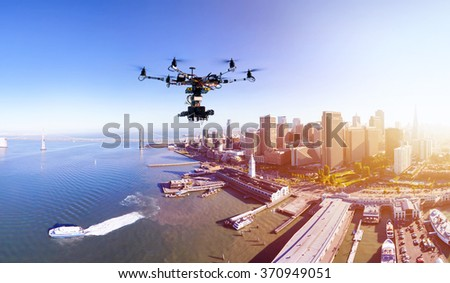 Professional drone with the cinema camera flying over San-Francisco pears and the financial district at the summer sunset.