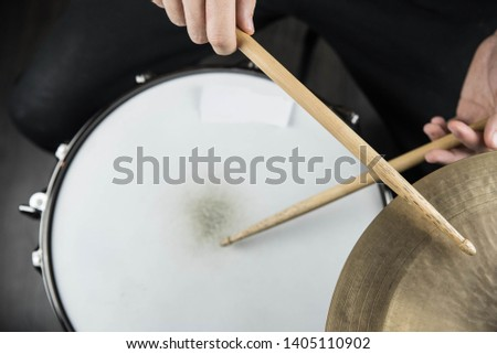 Professional drum set closeup. Man drummer with drumsticks playing drums and cymbals, on black wooden background