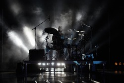 Professional drummer man behind the drum set playing drums solo in the dark with smoke in the background on a concert stage. Musician rehearsing. Music rock band live concert scene with stage lights