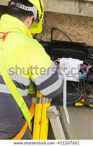professional electrician worker with safety protective equipment  to install internet , tv and phone with optical fiber system in the building facade #411207661