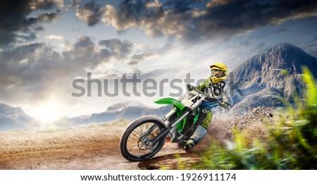 Professional enduro bike rider on action. Turn on sand terrain. ストックフォト ©