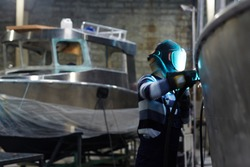 Professional engineer in protective workwear welding side detail of new boat in factory