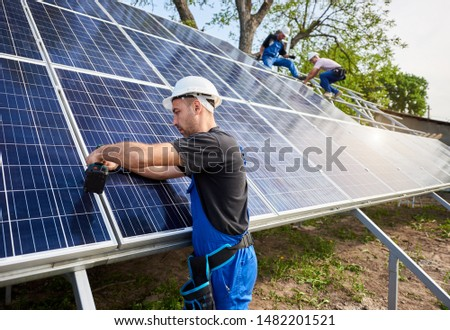 Professional engineer technicians installing exterior solar photo voltaic panel to metal platform on blue sky background. Stand-alone solar system installation, efficiency and professionalism concept.