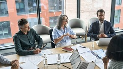 Professional executive businesspeople discuss corporation project planning sit at meeting table in boardroom. Company managers brainstorm financial plan working together with document papers in office