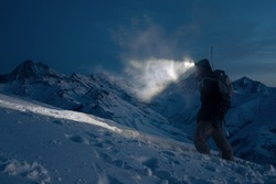 Professional expeditor commit climb on snowy mountains at night and lights the way with a headlamp. Wearing ski wear, backpack and a snowboard behind his back. Backcountry and ski touring