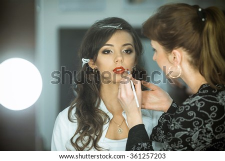 Professional expert,makeup artist prepares very beautiful,young,well-known,glamorous,stunning model for filming shooting for cover of fashion magazine VOGUE,does make-up,makes up lips,art,eyes,white.