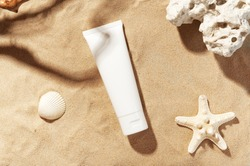 Professional face skincare. Unbranded flacon with moisturizing liquid. Cream or lotion. Mockup style. Summer decorations, seashell and starfish, sand background. Beauty concept