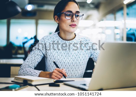 Professional female administrative manager reading financial news on website sitting at desktop,smart businesswoman in eyewear for vision protection working via laptop computer making online research #1051141724
