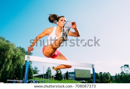Professional female athlete hurdler running jumping over hurdles