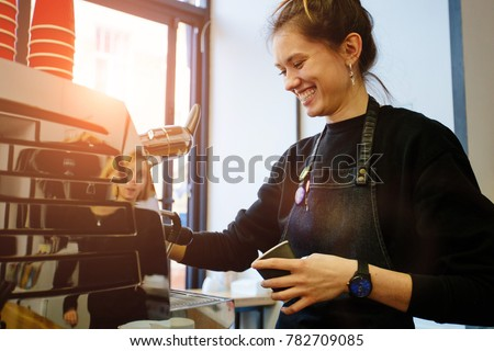 Professional female barista holding metal jug warming milk using the coffee machine. Positive smilingwoman preparing coffee at counter. Real people model concept.