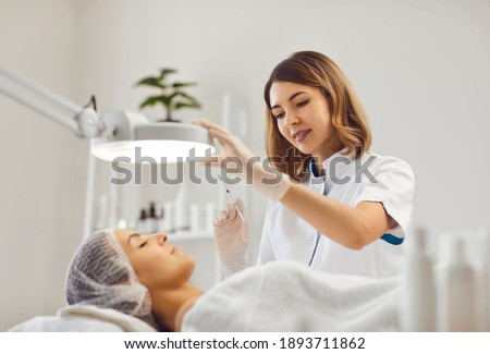 Professional female beautician makes a rejuvenating injection to a young woman who lies relaxed with her eyes closed in a modern beauty salon. Concept of smoothing wrinkles with injections.