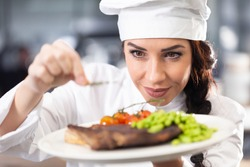 Professional female chef in a hat makes final touches on a freshly made steak before serving.