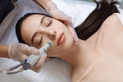 Professional female cosmetologist doing hydrafacial procedure in Cosmetology clinic.