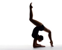 Professional female gymnast in sportswear performs a handstand. Training, elements of gymnastics, acrobatics on a white background. Sports motivation, stretching, splits. Banner for advertising