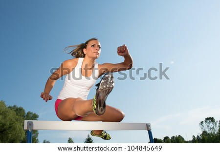 Professional female hurdler in action - stock photo