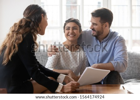 Professional female lawyer answering questions of curious indian woman sitting on couch with husband. Financial advisor consulting diverse young family couple about deal, explaining contract details.