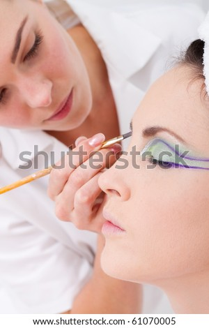 professional female makeup artist applying makeup to model's face