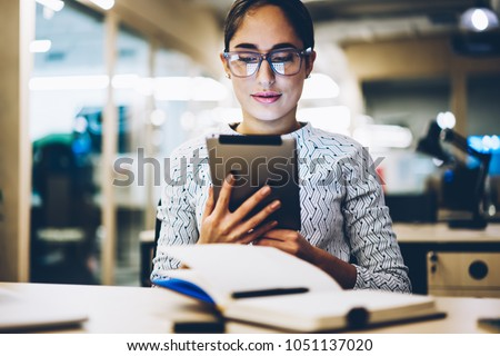 Professional female manager reading publication on web page browsed on digital tablet making research in office, skilled administrative woman checking mail via portable pc sending feedback #1051137020