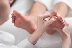 Professional female masseur giving reflexology massage to woman foot.